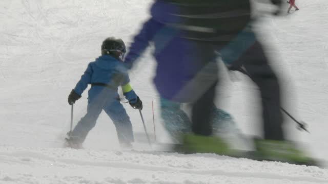 vídeos de stock e filmes b-roll de rear view of people skiing down ski slope - enfeites para a cabeça