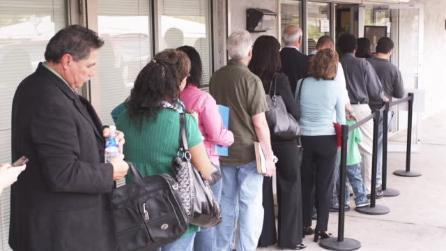 ms, rear view of people waiting in line at unemployment office, phoenix, arizona, usa - fare la fila video stock e b–roll