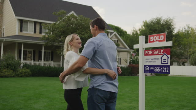 rear view of proud couple hugging on lawn of sold house for sale / pleasant grove, utah, united states - 売り出し中点の映像素材/bロール