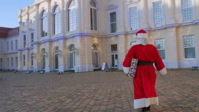 rear view of santa claus carrying gift in front of charlottenburg palace - weihnachtsmann stock-videos und b-roll-filmmaterial