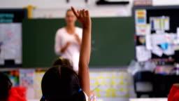 Rear view of schoolgirl raising hand in the classroom 4k