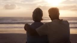 Rear View Of Senior Couple On Beach Watching Sun Set Over Ocean