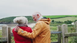 Rear view of senior couple resting by gate and looking at view as they walk along coastal path in autumn - shot in slow motion