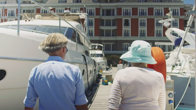 rear view of senior couple walking at harbor - pier stock videos & royalty-free footage