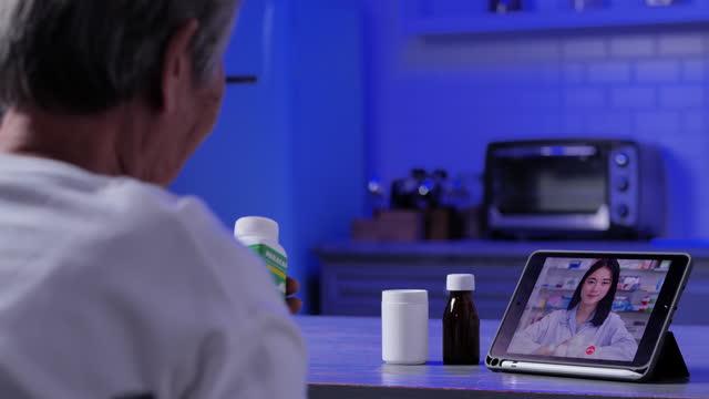 vidéos et rushes de vue arrière de grand-mère aînée âgée 83 ans parlant au travailleur de la santé par vidéoconférence à la maison pendant la distanciation sociale utilisant l'ordinateur de labtop et la technologie de vidéoconférence la nuit. soins de santé pou - new age concept