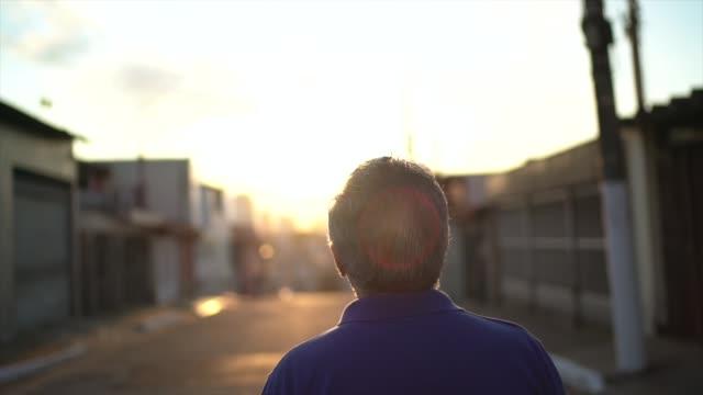 vídeos de stock, filmes e b-roll de opinião traseira o homem sênior que anda e que olha afastado ao pensar sobre a vida - vista traseira