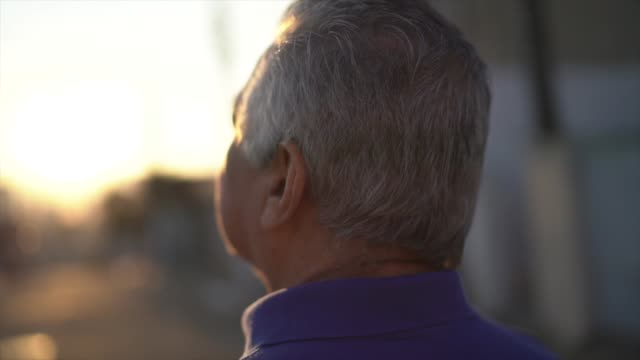 rückansicht des seniors, der beim nachdenken über das leben geht und wegschaut - 65 69 jahre stock-videos und b-roll-filmmaterial