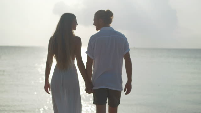 rear view of silhouette to couples age 25-29 yearold of latin american and hispanic ethnicity walk and holding hand with romance along edge of sunset sea on sand beach. happy family holidays. non-caucasian honeymoon concept. - wonderlust stock videos & royalty-free footage