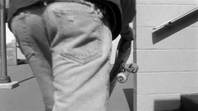 vídeos de stock, filmes e b-roll de rear view of skater holding skateboard / running toward top of stairs and jumping onto board - só um menino adolescente