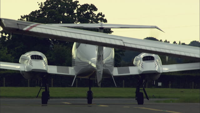 stockvideo's en b-roll-footage met cu pan rear view of small private planes diamond da42 on runway / dorchester, dorset, united kingdom - luchtvaartuig