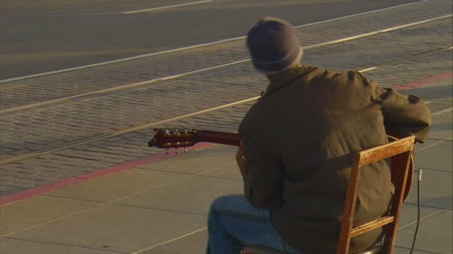 vidéos et rushes de ms rear view of street performer playing guitar at fisherman's wharf, san francisco, california, usa - california street san francisco