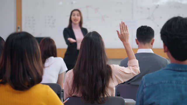 rear view of student raising hand and asking teacher for questions during class - high up stock videos & royalty-free footage