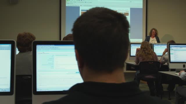 vídeos de stock, filmes e b-roll de ms pan rear view of students in college computer lab, orem, utah, usa - orem utah