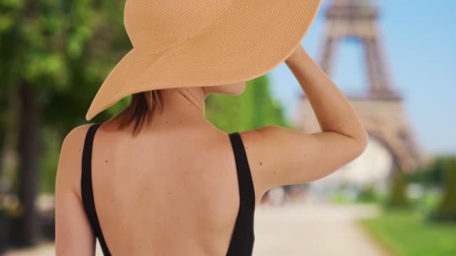 vídeos y material grabado en eventos de stock de rear view of stylish caucasian girl in paris wearing floppy sunhat - accesorio de cabeza