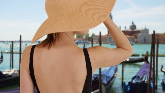 vídeos y material grabado en eventos de stock de rear view of stylish woman tourist by the grand canal smiling - accesorio de cabeza