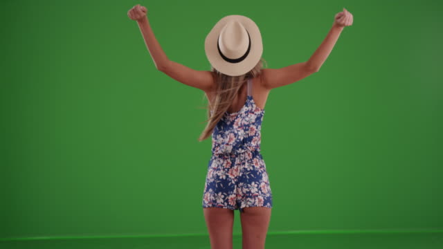 vídeos de stock, filmes e b-roll de rear view of stylish woman with arms outstretched turning around on greenscreen - braço humano