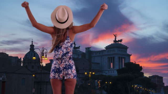 Rear view of stylish woman with outstretched arms feeling wind in Rome, Italy