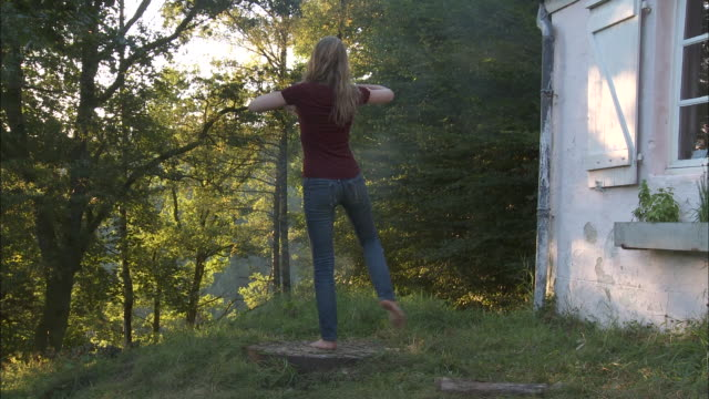 ws rear view of teenage girl (14-15) doing sun salutation outdoors, bouillon, belgium - sun salutation stock videos and b-roll footage
