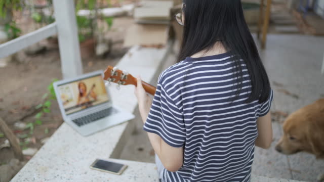 vídeos de stock, filmes e b-roll de visão traseira de menina adolescente jogando ukulele com seu amigo ou professor usando laptop de teleconferência em covid-19 ou situação de vírus corona - ukulele