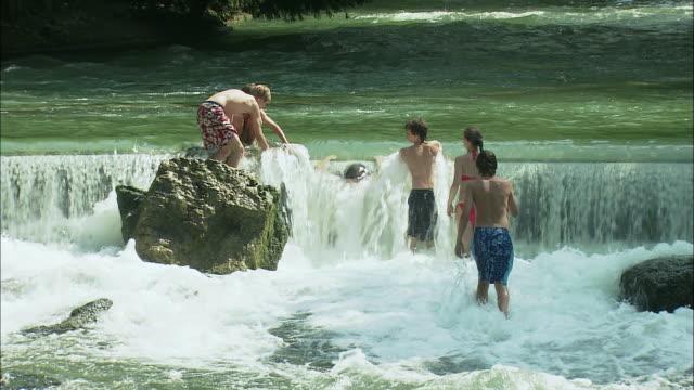 ms rear view of teenagers bathing in river in englischer garten (english garden), munich, bavaria, germany - ミュンヘン エングリッシャーガルテン点の映像素材/bロール