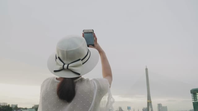 rear view of thai tourist is photographing the bridge by using smart phone in bangkok before sun set - dorso umano video stock e b–roll