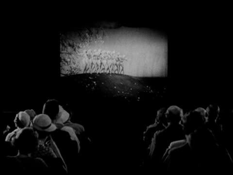 vidéos et rushes de b/w ws 1936 rear view of theater audience watching movie - 1930