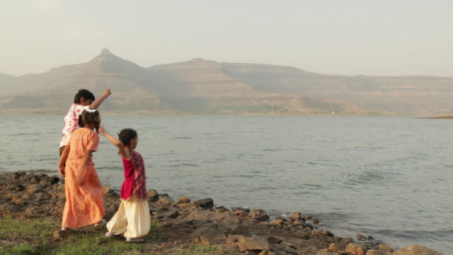 Rear view of three kids throwing stones in the river