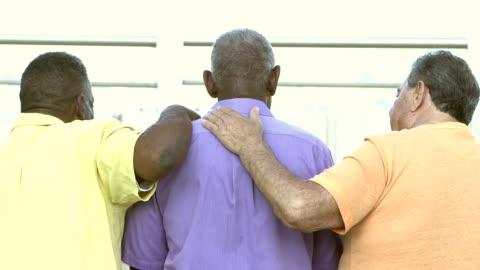 rear view of three multi-ethnic senior men on bench - arm around stock videos & royalty-free footage