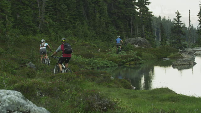 WS Rear view of three people cycling along river, Coast Mountains, Squamish, British Columbia, Canada