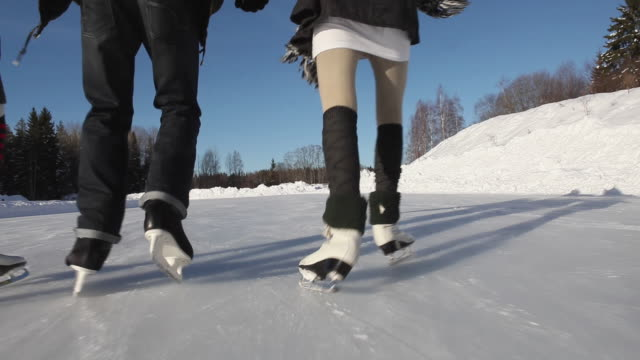 ws ms la pov rear view of three people ice skating on outdoor rink / gavle, gastrikland, sweden - ice rink stock videos and b-roll footage