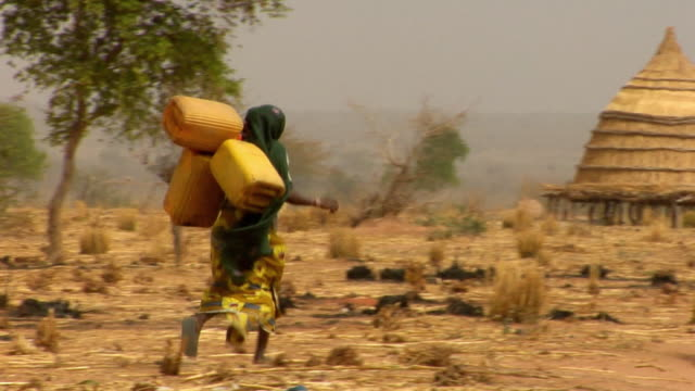 ws, pan, rear view of three women carrying containers with water towards village, niamey, niger - ニアメ点の映像素材/bロール