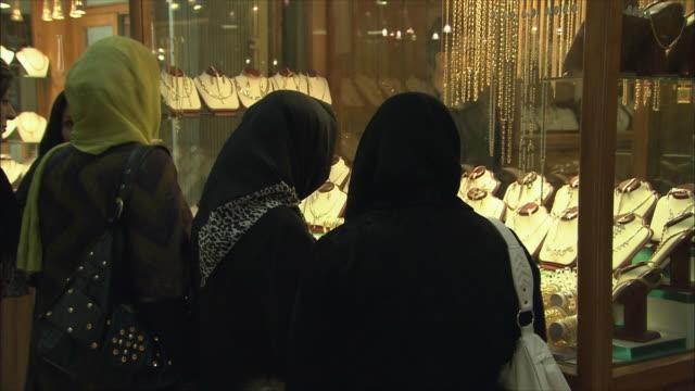 cu rear view of three women looking at jewelry store display in grand bazaar, isfahan, iran - skåp med glasdörrar bildbanksvideor och videomaterial från bakom kulisserna