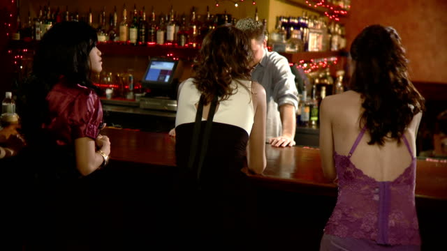 ms rear view of three women talking to bartender at bat counter, jacksonville, florida, usa - maschio con gruppo di femmine video stock e b–roll
