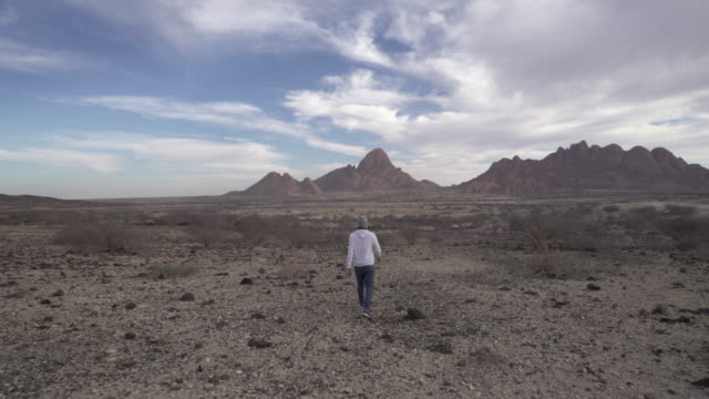 rear view of tourist walking towards mountains against sky, man is on vacation at remote area - spitzkoppe, namibia - rear view stock videos & royalty-free footage