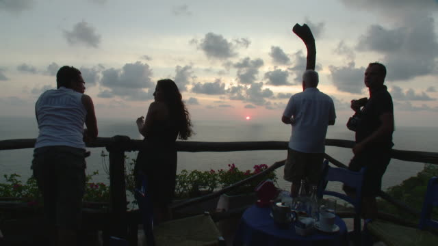 WS Rear view of tourists watching sunset from restaurant patio over ocean / Acapulco, Guerrero, Mexico