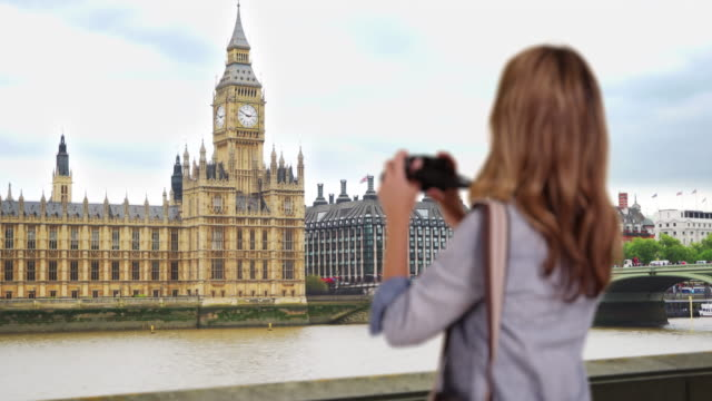 rear view of travel photographer taking picture of the big ben - big ben点の映像素材/bロール