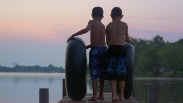rear view of two boys rolling inner tubes down pier at dusk / long pond, new york - 浮き輪点の映像素材/bロール