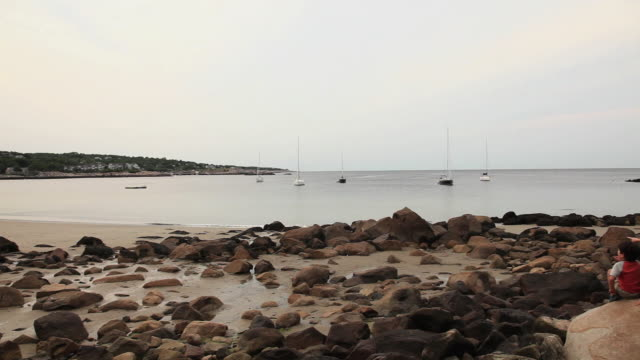 ws pan rear view of two boys sitting on rocky beach / rockport, massachusetts, usa - rockport massachusetts stock videos & royalty-free footage