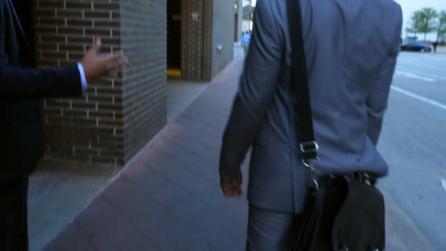stockvideo's en b-roll-footage met ms ts rear view of two businessmen in discussion while walking down city sidewalk - attaché
