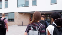 Rear View Of Two Female High School Students Walking Into College Building Together