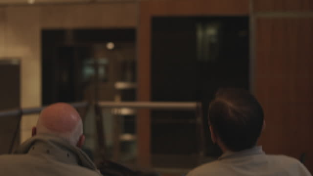 CU TU Rear view of two men watching data board of Australian Stock Exchange (ASX) / Sydney, New South Wales, Australia