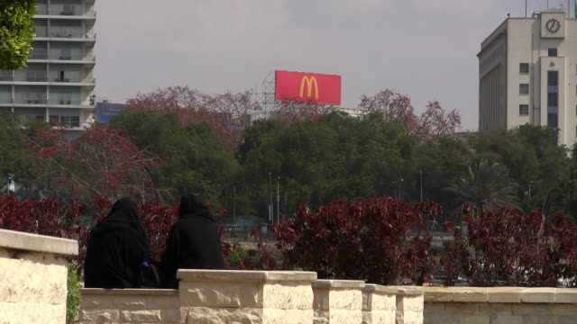 zi, ms, rear view of two muslim women dressed in all black sitting on wall, cairo egypt - mcdonald's stock videos and b-roll footage