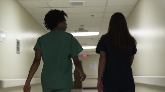 MS Rear view of two nurses walking through hospital corridor / Payson, Utah, USA