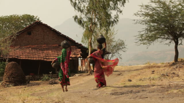 rear view of two rural woman carrying earthen pot on her head  - village stock videos & royalty-free footage