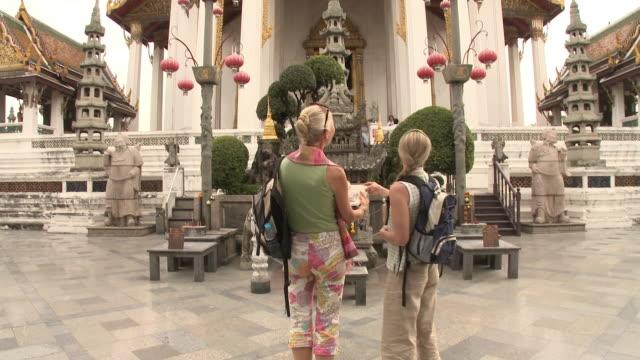 ZO WS Rear view of two women reading guidebook at Wat Phra Kaew (Temple of the Emerald Buddha), Bangkok, Thailand