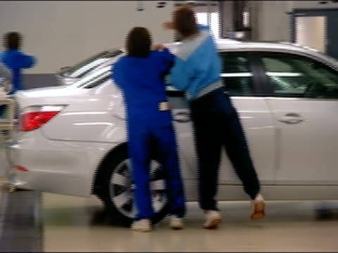 vidéos et rushes de rear view of two workers detailing roof of sedan in bmw factory / pan to worker detailing mini / tokyo, japan - usine automobile