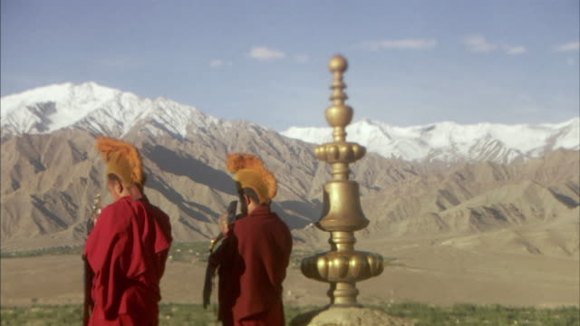 MS, Rear view of two Yellow hat Tibetan Buddhist monks playing gjalings in mountain landscape, Ladakh, Jammu and Kashmir, India