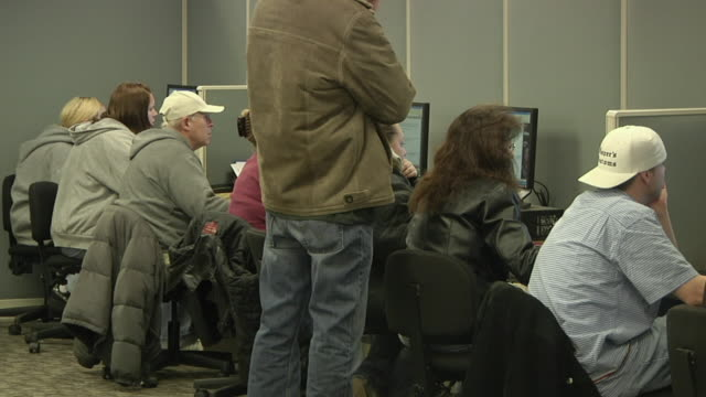vidéos et rushes de ms rear view of unemployed workers using computer at michigan works job center, jackson, michigan, usa - chômage