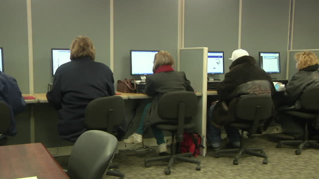 vidéos et rushes de ws pan rear view of unemployed workers using computers at michigan works job center, jackson, michigan, usa - chômage