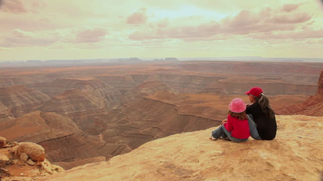 WS PAN Rear view of woman and girl (6-7) sitting on edge of canyon enjoying views / Muley Point, Utah, USA